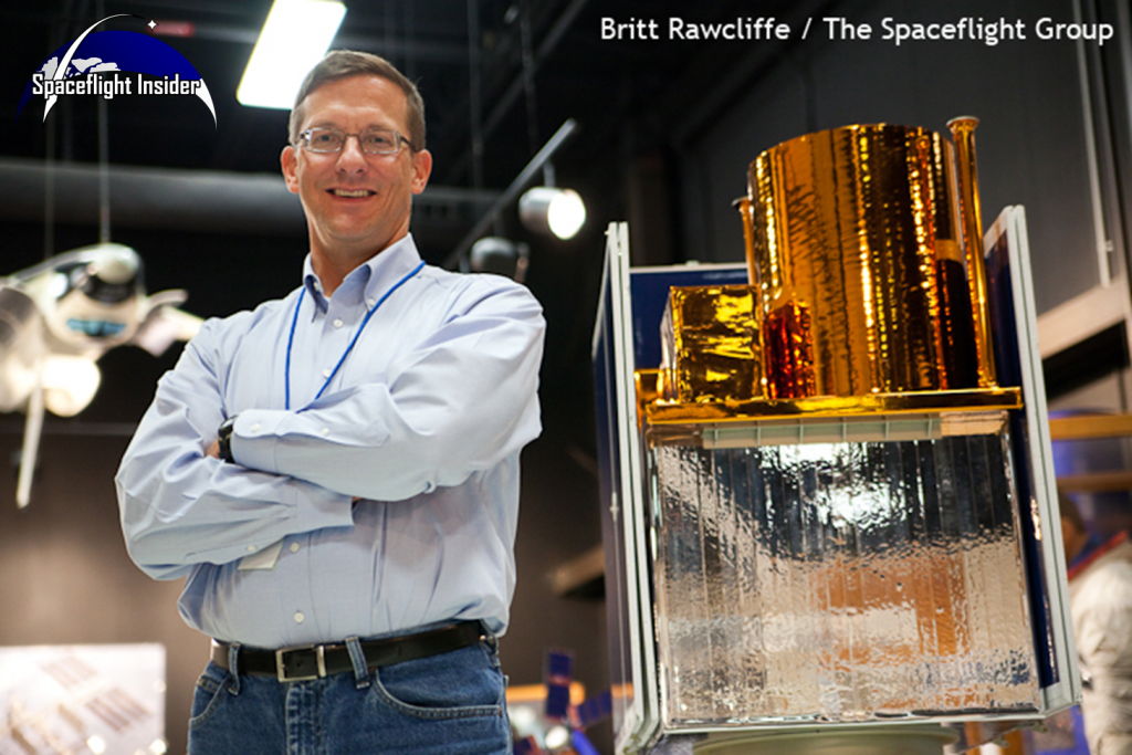 a Steven A. Smith, director of Military Space at Ball Aerospace poses with a model of the STPSat-2, the predecessor of the STPSat-3 that flew on the ORS-3 mission.