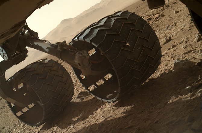 The Curiosity rover's return to operations after the recent electrical issue, came with this photo. It was acquired by the MAHLI camera that is mounted on the rover's robotic arm, on the mission's Sol 463 (24 November 2013). Some expected wear and tear on the middle wheel is visible. Image Credit: NASA/JPL-Caltech